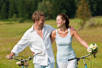 Romantic couple walking with old bike in meadow