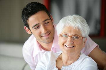 Portrait d'une femme senior souriante près d'un jeune homme