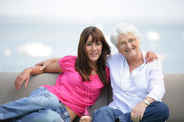 femme senior assise sur un canapé près d'une jeune femme