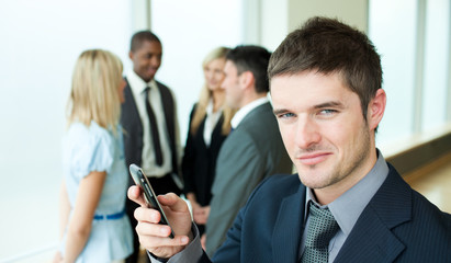 Happy businessman sending a text in office