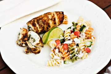 Fusilli salad served with stuffed chicken and a slice of lime.