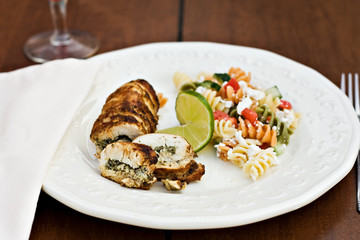 Peppered stuffed chicken with a slice of lime and fusilli salad