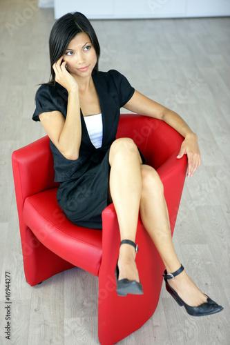 femme t l phonant assise sur un fauteuil photo libre de. Black Bedroom Furniture Sets. Home Design Ideas