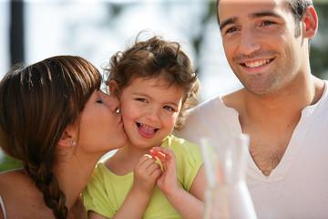 Couple embrassant une petite fille sur la joue