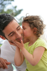 Petite fille embrassant un homme sur la joue