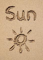 The word sun and a sun symbol drawn on a beach.