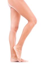 Nackte Beine von Frau auf weiß, ein Knie angezogen