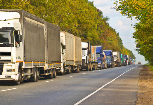 queue of lorry cargo trucks, commercial transports on landscape road