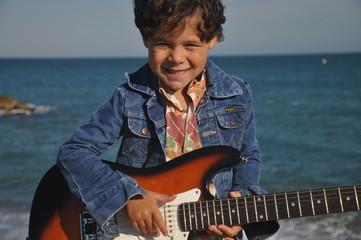 enfant 5 ans qui joue de la guitare électrique fond mer
