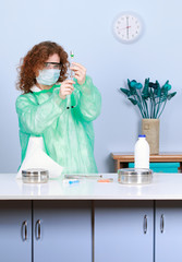woman in a medical mask  filling up syringe