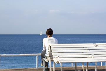 Frau auf Bank mit Segelboot am Horizont
