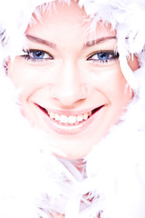 laughing young woman with white boa over her face