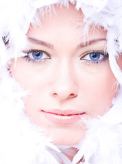 young woman with blue eyes and white boa over her face