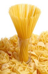 Spaghetti in glass standing on several types of pasta