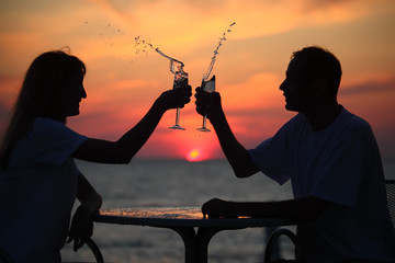 silhouettes of man and woman splash out drink from glass on sea