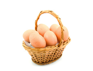 cane basket with chicken eggs over white background