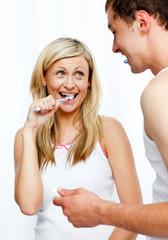 Couple having fun cleaning their teeth