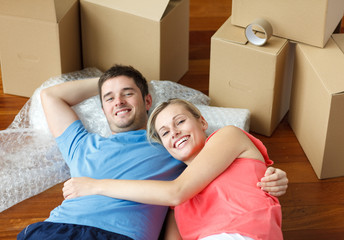 Happy couple lying on floor after moving house smiling at the ca