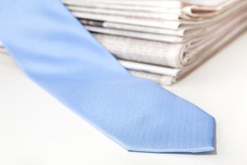 Zeitungen unter blauer Kravatte