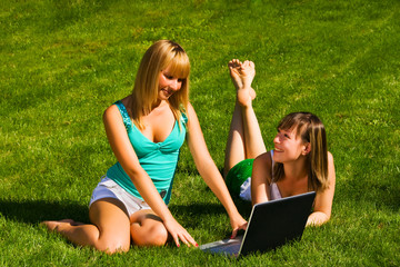 Two young girls on the grass with notebook