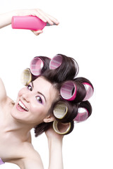 Laughting girl with colorful hair-curlers and hair spray