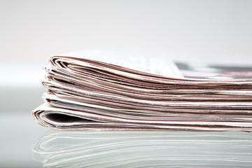 Zeitungen auf einem Glastisch