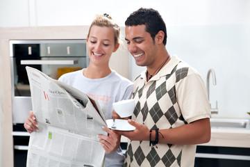 junges Paar liest gemeinsam Zeitung