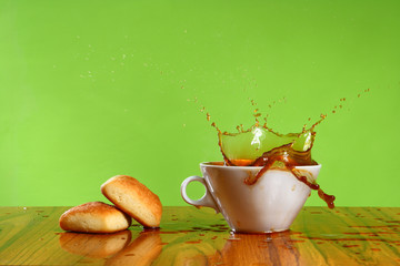 coffee splash on a green background in a white cup
