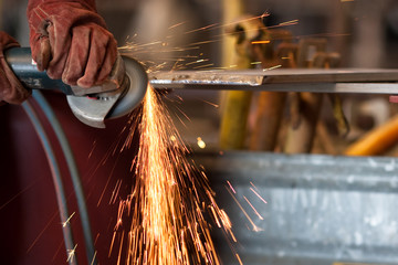 worker grinding metal and sparks