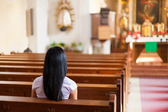 Frau betet in einer Kirche