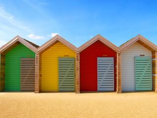 Four colourful beach huts