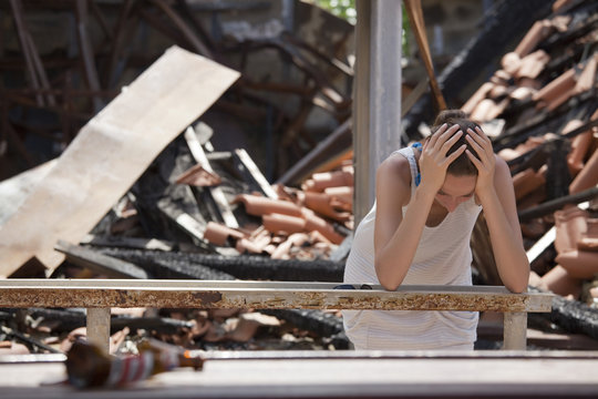 sad woman and destroyed house