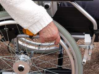 Hand am Rad eines Rollstuhles