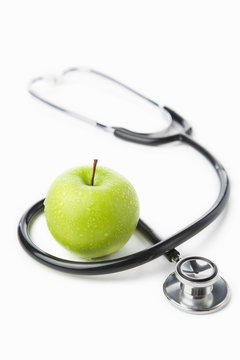 Stethoscope and green apple over white