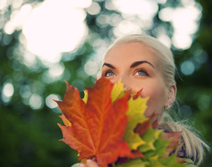 Beautiful romantic woman with golden autumn leaf close-up portra