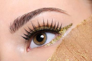 female eye witha false eyelashes and golden make-up