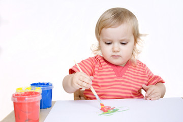 Serious baby girl painting with a brush