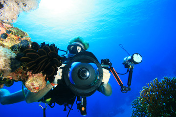 Scuba Diver with digital SLR camera in housing with strobes