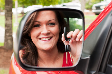 Attractive Brunette Holding Keys in Vehicle Mirror