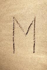 Alphabet letter M handwritten in sand