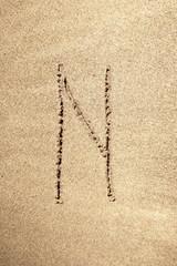 Alphabet letter N handwritten in sand