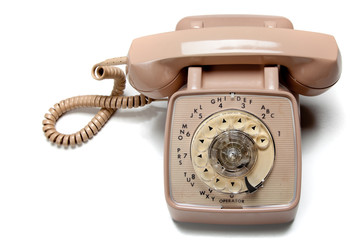 Old rotary telephone on white