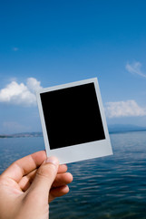 Photo in a hand on nature sea background