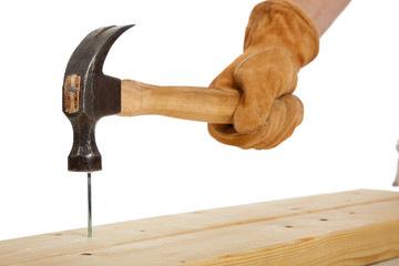 A gloved hand hammering a nail in a piece of wood