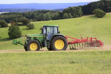 Traktor mit Grubber auf dem Acker