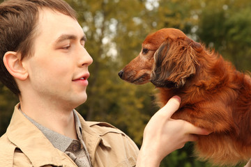 Young man and his adorable dachshund closeup