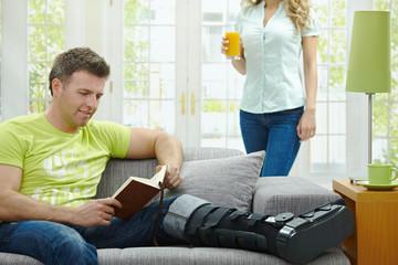 Man with broken leg reading book