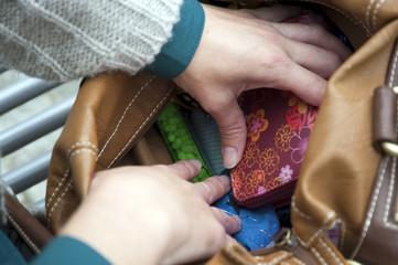 Frauenhände in der Handtasche