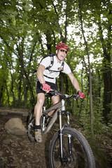 Mountain Biker bei einen Sprung im Wald