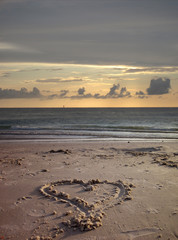 An image of heart shape drawing on the sand